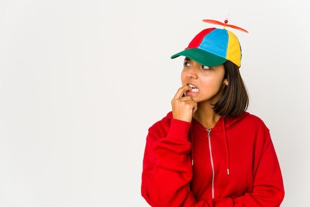 Giovane donna ispanica che indossa un berretto con elica isolata