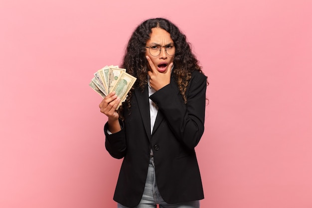 Giovane donna ispanica con la bocca e gli occhi spalancati e la mano sul mento, sentendosi spiacevolmente scioccata, dicendo cosa o wow. concetto di banconote in dollari
