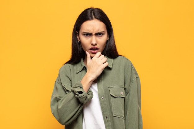 Giovane donna ispanica con la bocca e gli occhi spalancati e la mano sul mento, sentendosi spiacevolmente scioccata, dicendo cosa o wow