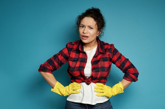 Giovane donna ispanica in guanti di gomma gialli per la pulizia con le mani sulla vita e sembrava scontenta nella telecamera