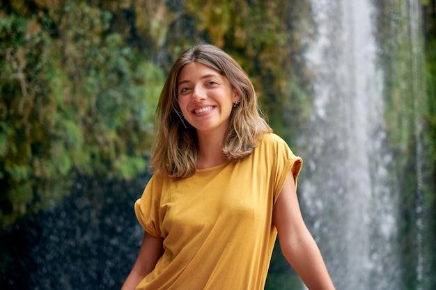Giovane donna ispanica con una maglietta gialla che sorride con una cascata sullo sfondo