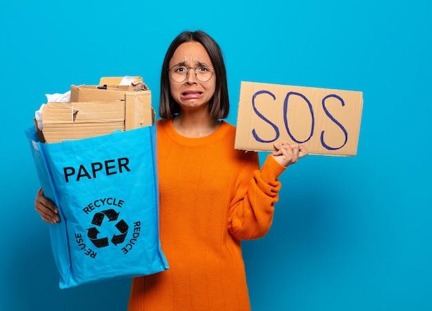 Giovane donna hispanis che tiene scheda sos e sacchetto di carta