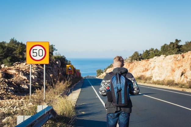 Giovane uomo di viaggio autostop lungo il percorso.