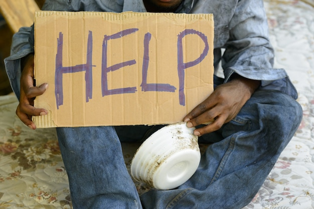 Giovane senzatetto uomo africano con cartello di cartone che chiede aiuto