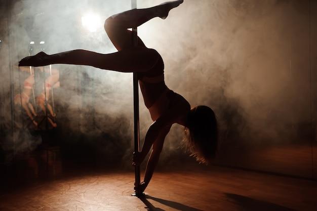 Giovane donna calda in lingerie sexy esegue sensuale pole dance.