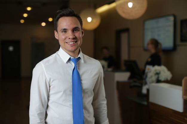 Un giovane amministratore d'albergo in camicia bianca e cravatta blu è in piedi contro la reception.