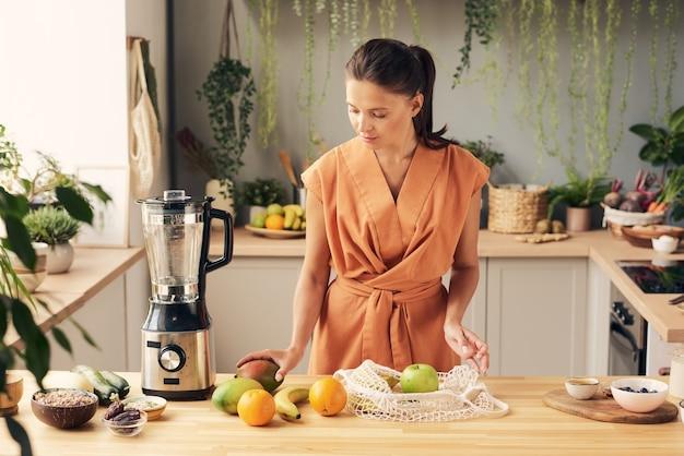 Giovane moglie di casa che prepara frutta fresca per il frullato