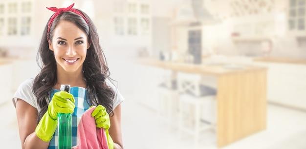 Giovane governante nella parte sinistra dell'immagine con la cucina sullo sfondo, che punta il detersivo verso la telecamera con un tappeto per la pulizia nell'altra mano.