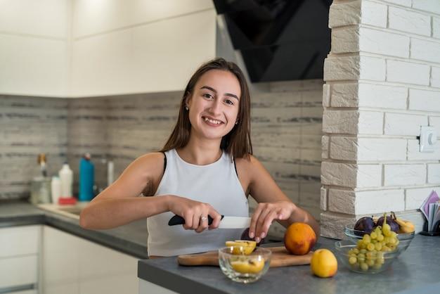 Giovane casalinga che taglia i frutti sulla tavola di legno mentre prepara il cibo sano per la colazione in cucina