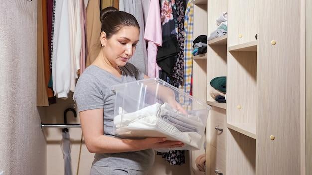 La giovane casalinga in maglietta grigia mette i vestiti piegati puliti su diversi scaffali di legno dal contenitore di plastica nella cabina armadio a casa primo piano