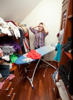 Giovane casalinga che ha mal di testa per un grosso mucchio di vestiti non stirati