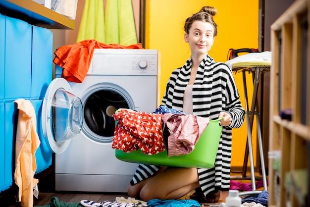 Giovane casalinga che tiene un cesto con i vestiti vicino alla lavatrice seduta per terra a casa