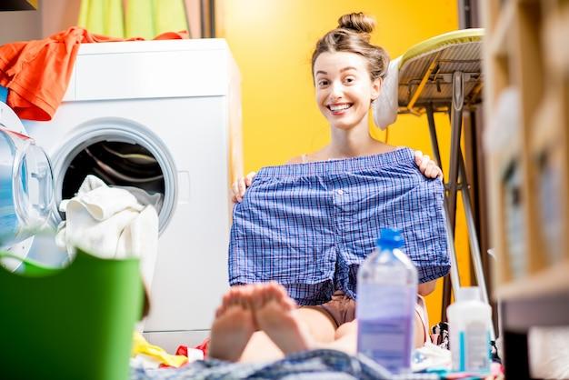 Giovane casalinga che tiene i pantaloni seduta vicino alla lavatrice con vestiti colorati a casa