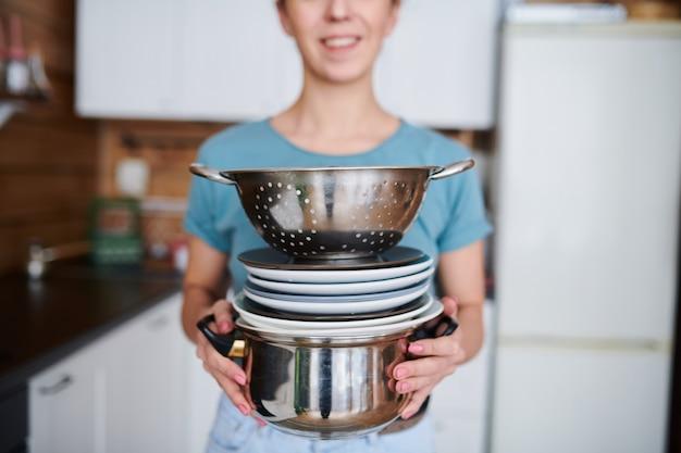 Giovane casalinga che tiene pila di piatti puliti e stoviglie