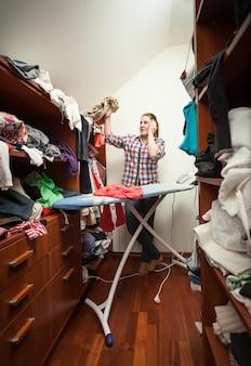 Giovane casalinga che guarda i vestiti non stirati all'armadio
