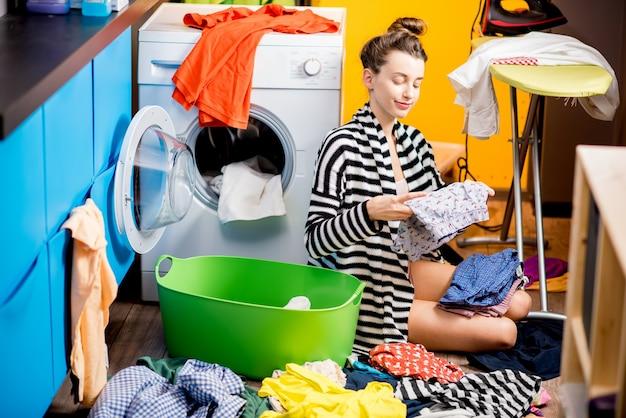 Giovane casalinga che mette insieme i vestiti seduti vicino alla lavatrice con vestiti colorati a casa