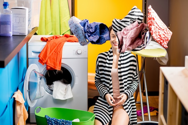 Giovane casalinga seduta vicino alla lavatrice con vestiti volanti a casa