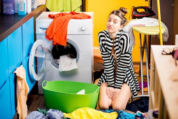 Giovane casalinga seduta tristemente vicino alla lavatrice con molti vestiti colorati sul pavimento di casa