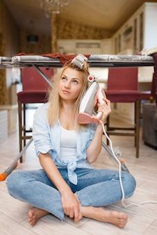 Giovane casalinga con il ferro da stiro al posto del telefono. donna che fa i lavori domestici a casa. la persona di sesso femminile stira i vestiti in cucina in casa