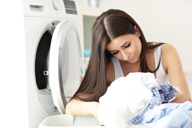 Giovane casalinga con il bucato accanto alla lavatrice