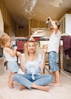 Giovane casalinga con bambini giocosi in cucina. donna con bambino che fa i lavori domestici a casa insieme. persona di sesso femminile con figlia che si diverte a casa sua