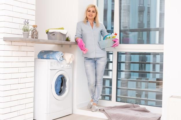 Una giovane casalinga con lavatrice e vestiti