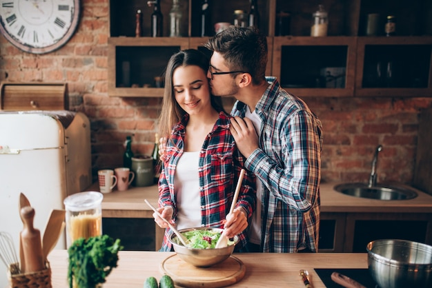 Giovane marito che bacia la moglie in cucina mentre lei cucina la colazione. uomo e donna che preparano insalata di verdure, famiglia felice insieme