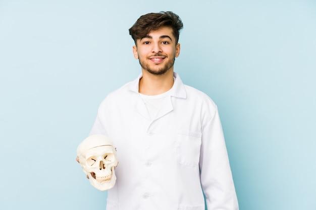 Uomo giovane medico ian in possesso di un teschio felice, sorridente e allegro.