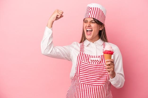 Giovane gelatiera donna che tiene il gelato isolato su sfondo rosa alzando il pugno dopo una vittoria, concetto vincitore.