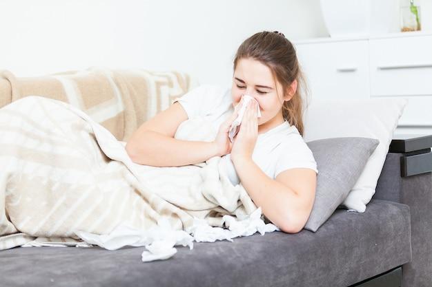 Giovane donna malata sdraiata a letto e starnutisce in un fazzoletto di carta