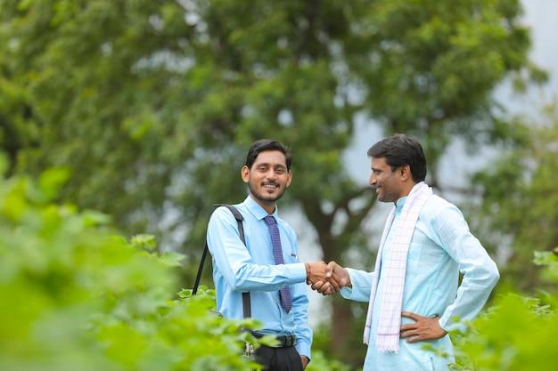 Il giovane agronomo o banchiere indiano stringe la mano con l'agricoltore al campo agricolo.