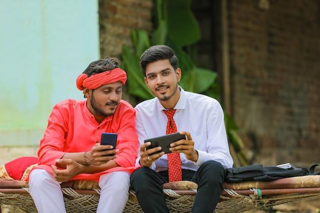 Giovane agronomo indiano o banchiere che mostra alcune informazioni all'agricoltore in smartphone
