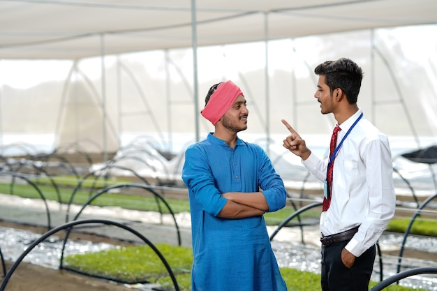 Il giovane agronomo indiano discute con l'agricoltore alla serra
