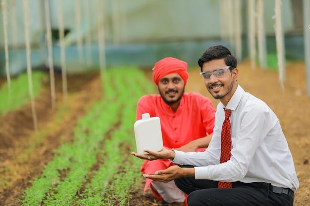 Giovane agronomo e agricoltore indiano che mostra la bottiglia alla serra