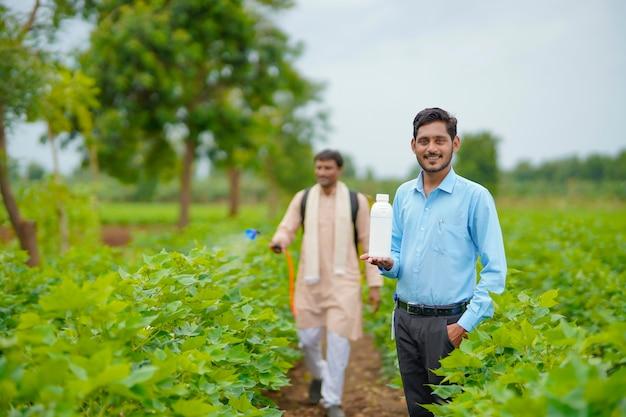 Giovane agronomo indiano che dà una bottiglia di fertilizzante liquido all'agricoltore e dice informazioni sul prodotto al campo agricolo verde.