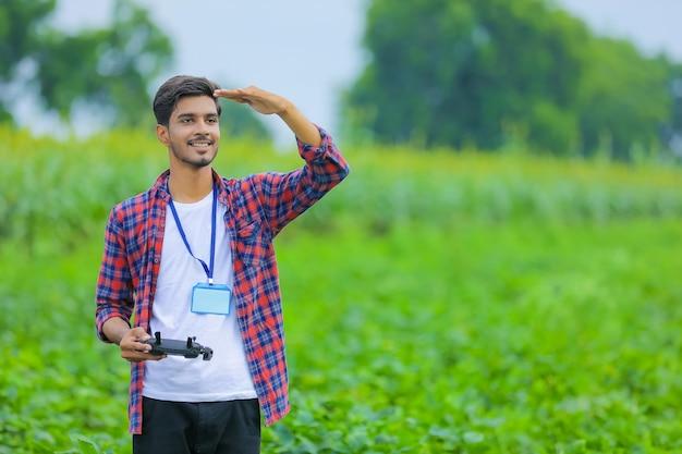 Il giovane agronomo indiano opera o controlla il drone volante in campo agricolo