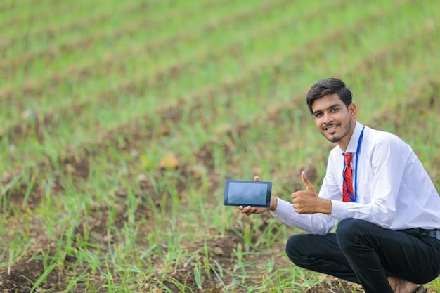 Giovane agronomo indiano che mostra smart phone al campo agricolo