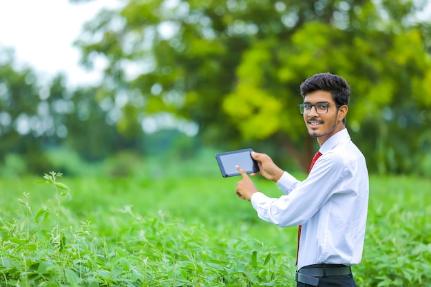 Giovane agronomo indiano che mostra smartphone al campo