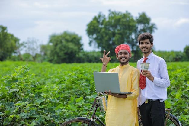 Giovane agronomo indiano che mostra alcune informazioni all'agricoltore nel computer portatile al campo di cotone