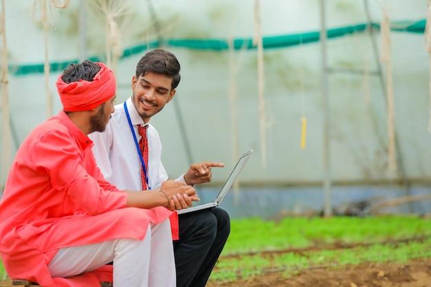 Giovane agronomo indiano che mostra alcune informazioni all'agricoltore nel computer portatile alla serra