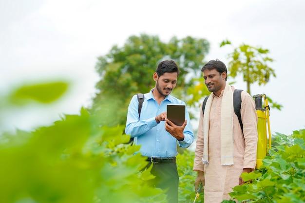 Giovane agronomo indiano che mostra alcune informazioni all'agricoltore in tablet al campo agricolo.