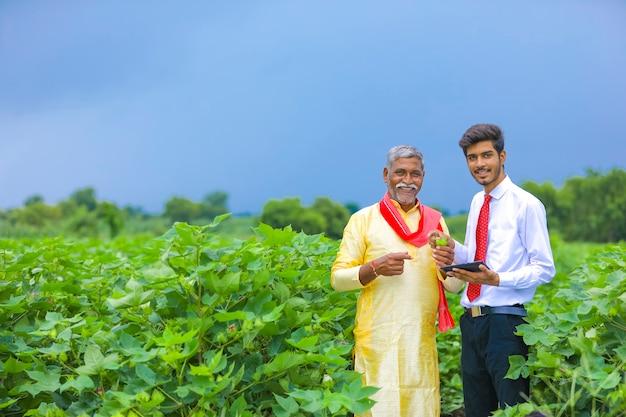 Giovane agronomo indiano con contadino al campo di cotone e mostrando alcune informazioni sul telefono cellulare