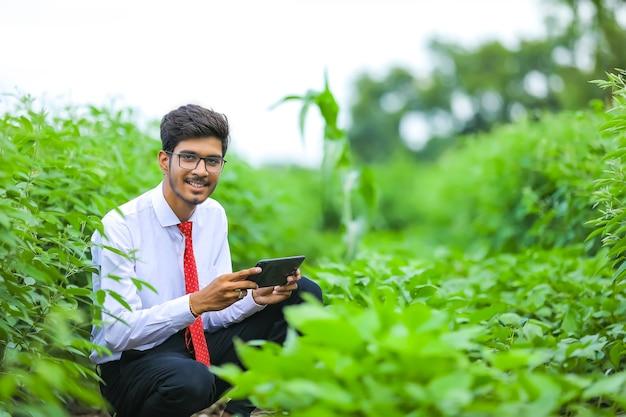 Giovane agronomo indiano con lo smartphone al campo