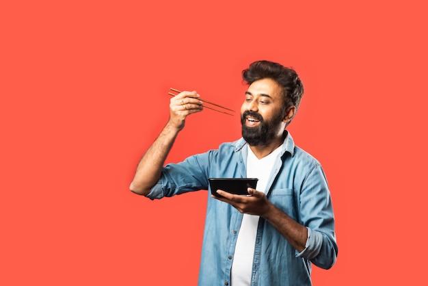 Giovane uomo asiatico indiano che mangia cibo da asporto nella scatola usando un cucchiaio o le bacchette, in piedi sul rosso