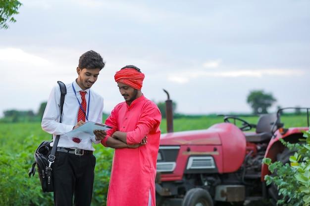Giovane funzionario di banca indiano che mostra il dettaglio della carta di prestito all'agricoltore al campo