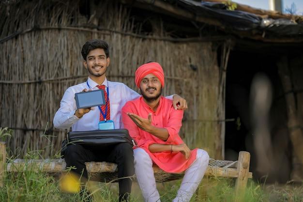 Giovane funzionario di banca indiano che mostra lo schermo mobile con l'agricoltore
