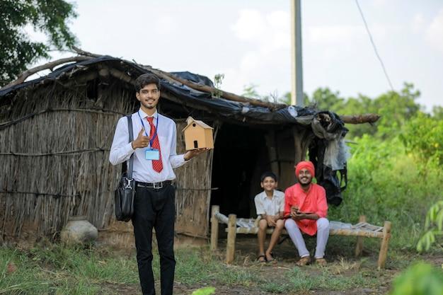 Un giovane banchiere o agronomo indiano visita una povera famiglia di contadini