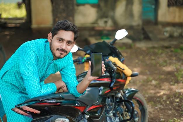 Giovane ragazzo indiano in usura etnica e mostrando smartphone con la nuova bici