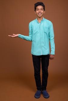 Giovane ragazzo indiano che indossa una maglietta blu cercando smart contro il marrone