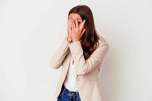 La giovane donna indiana di affari isolata su bianco sbatte le palpebre attraverso le dita spaventata e nervosa.